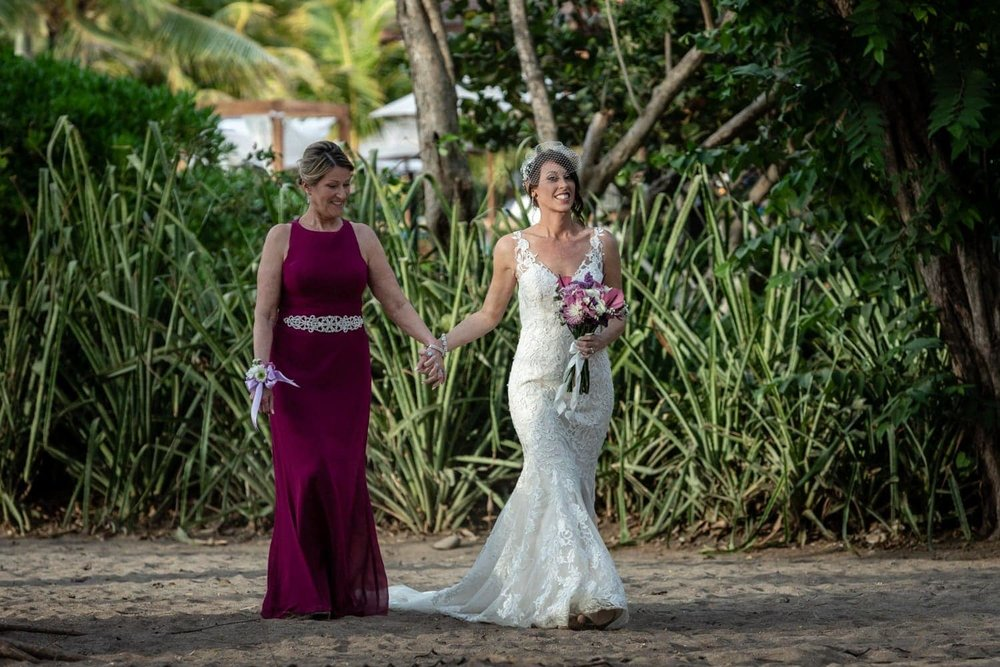 Mother walks daughter down aisle for her beach wedding.