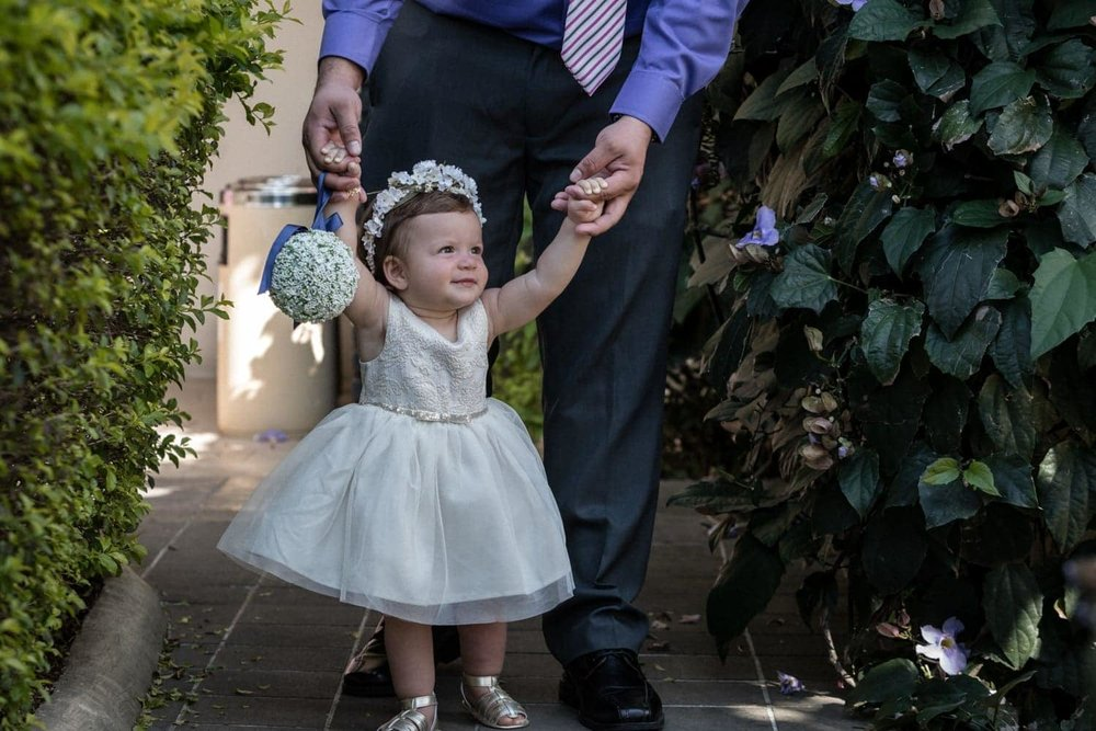 Father walks infant dressed for a wedding to ceremony site.