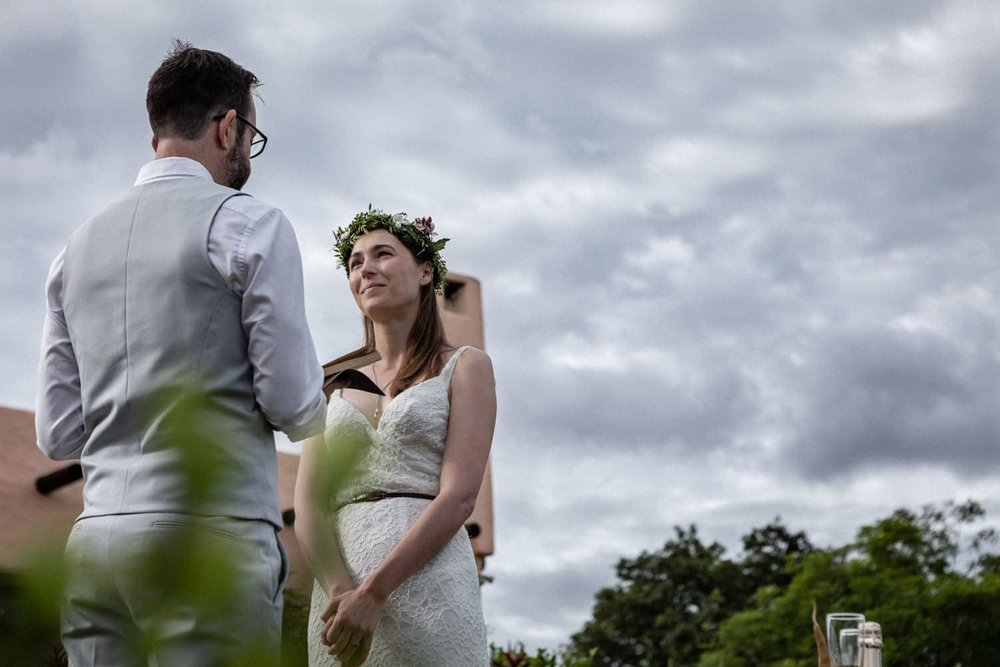 Couple says their wedding vows with dramatic sky overhead.