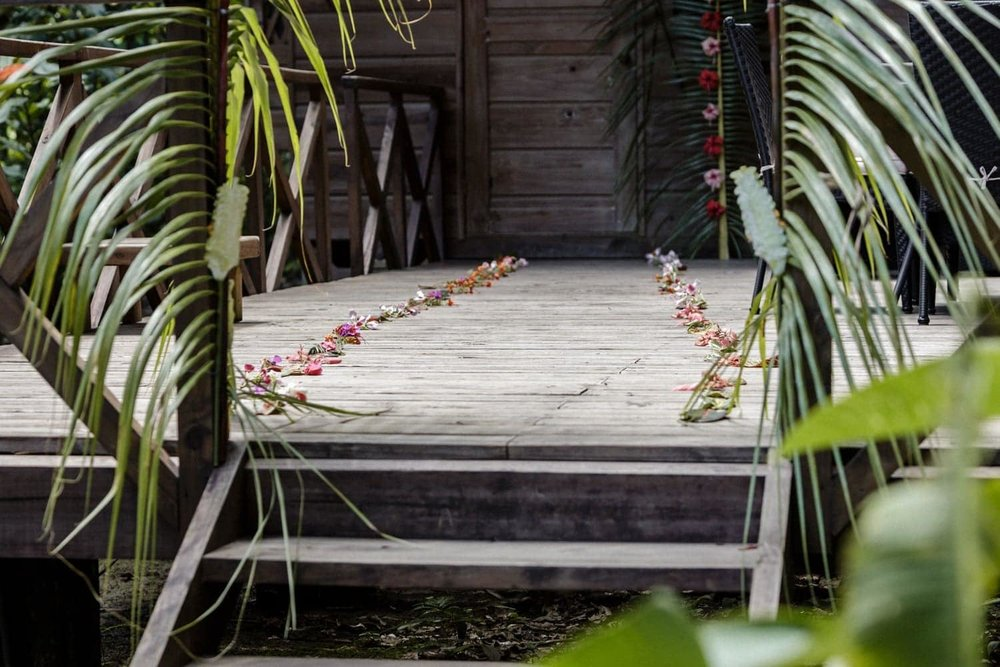 Flowers line path on wood deck leading to honeymoon suite.