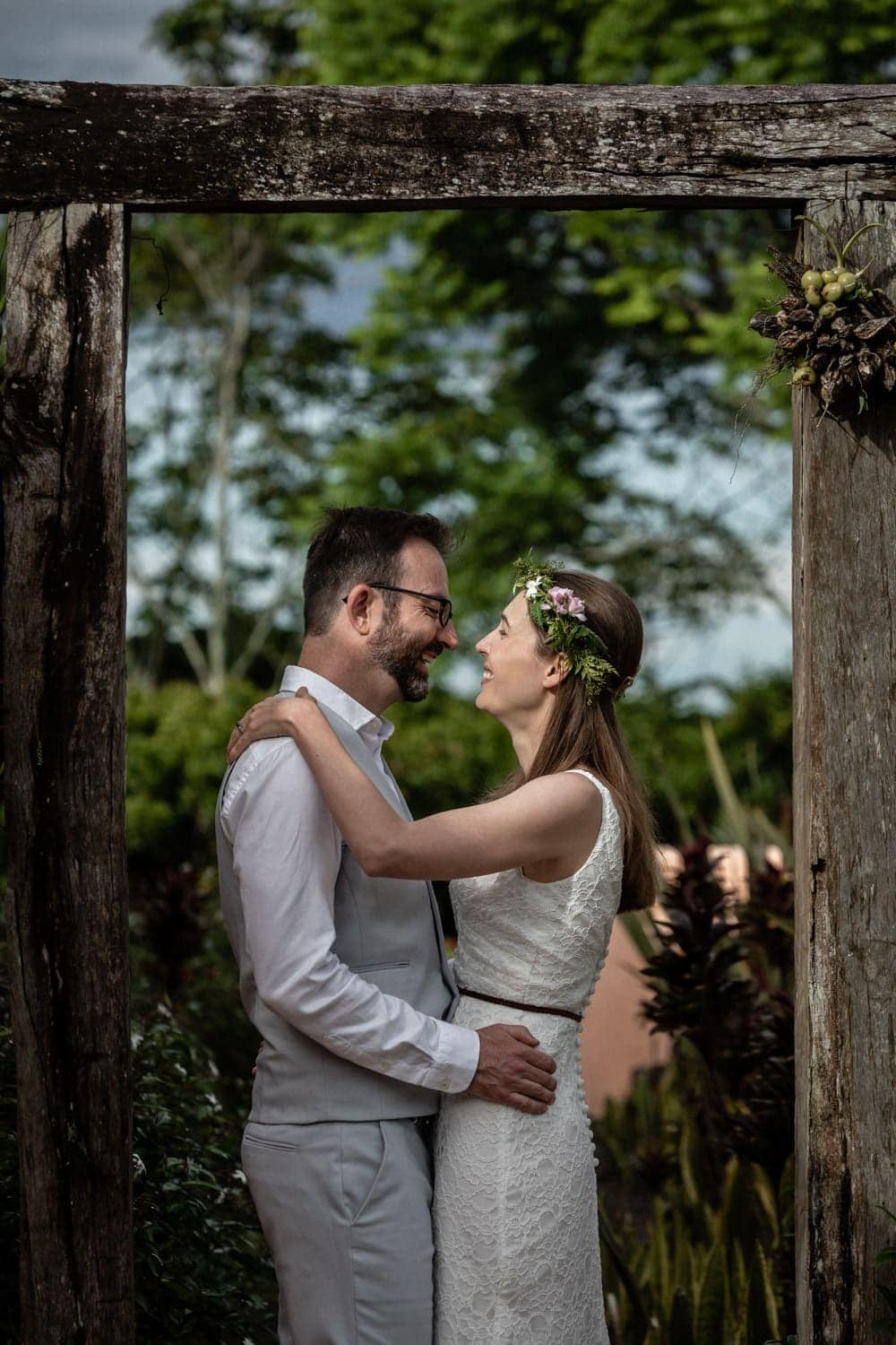 Bride and groom pose for wedding photo under rustic wooden arch.