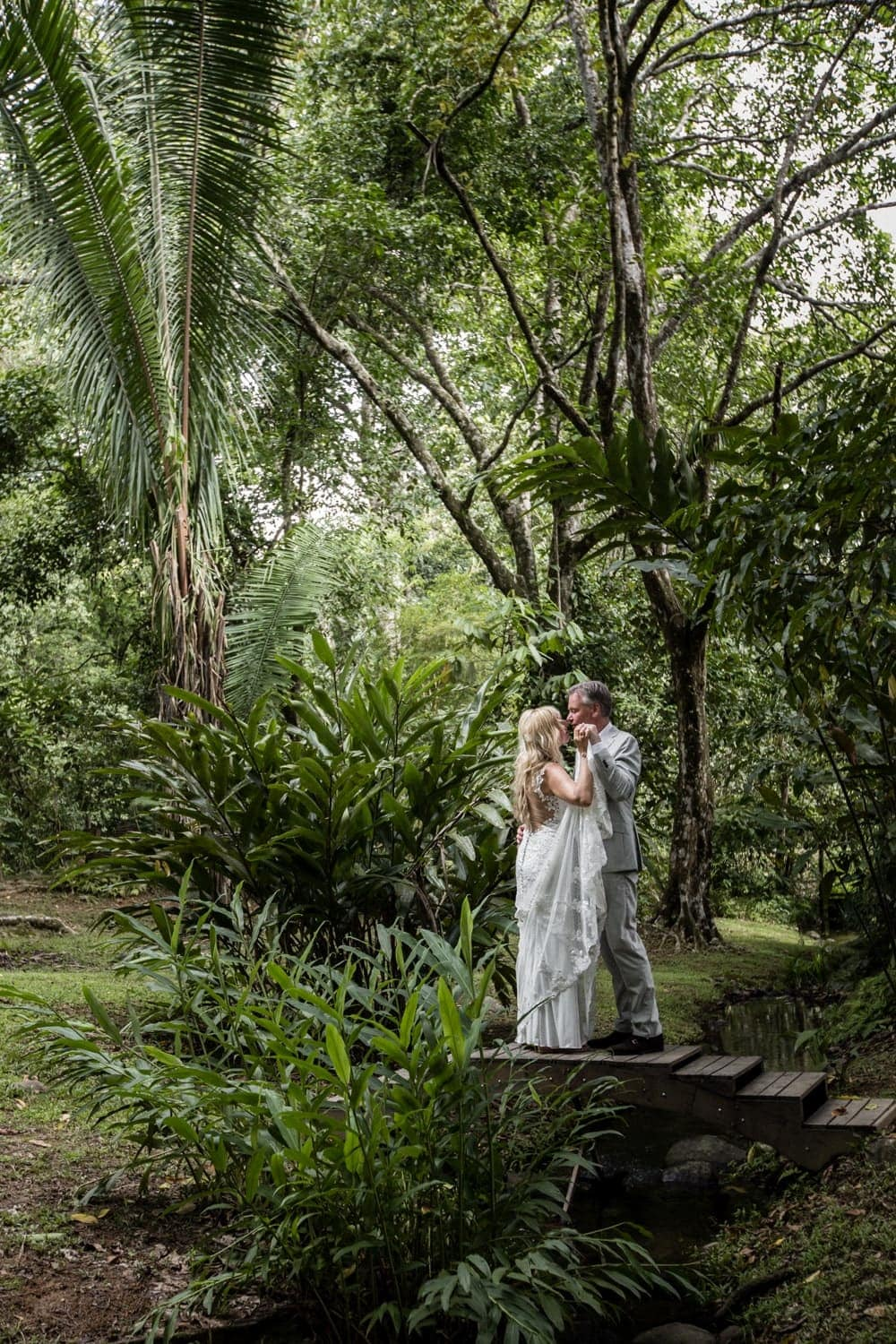 Couple poses for wedding picture on small bride in tropical garden.