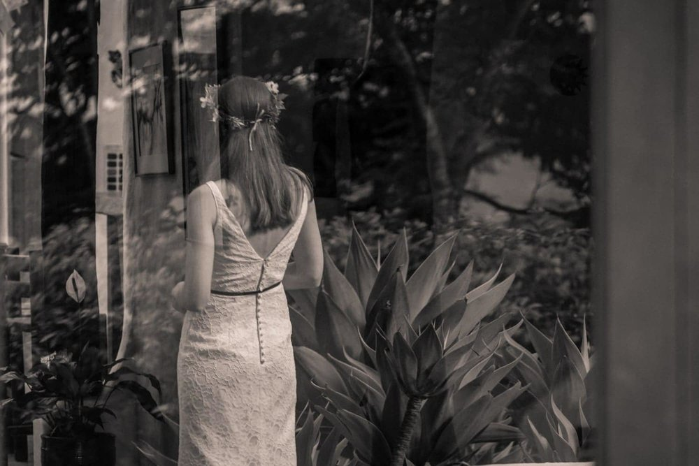 Reflection of bride in white wedding gown in tropical Costa Rica garden.