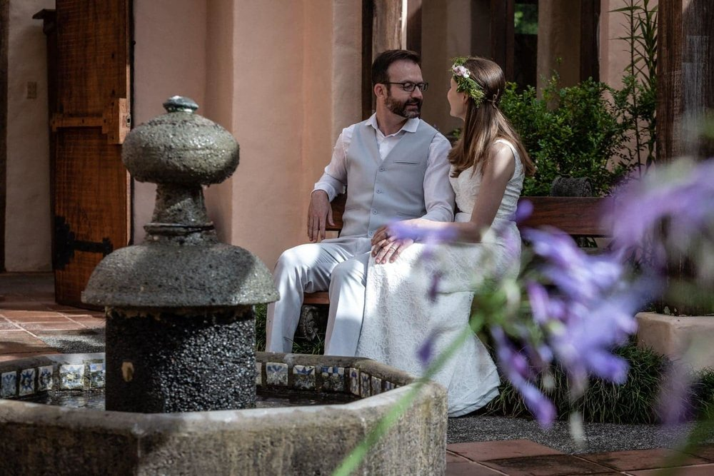 Couple pose for photo in courtyard after getting married in tropical garden.