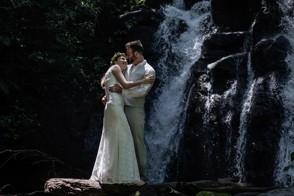 Bride and groom stand in front of water in rainforest in Costa Rica.
