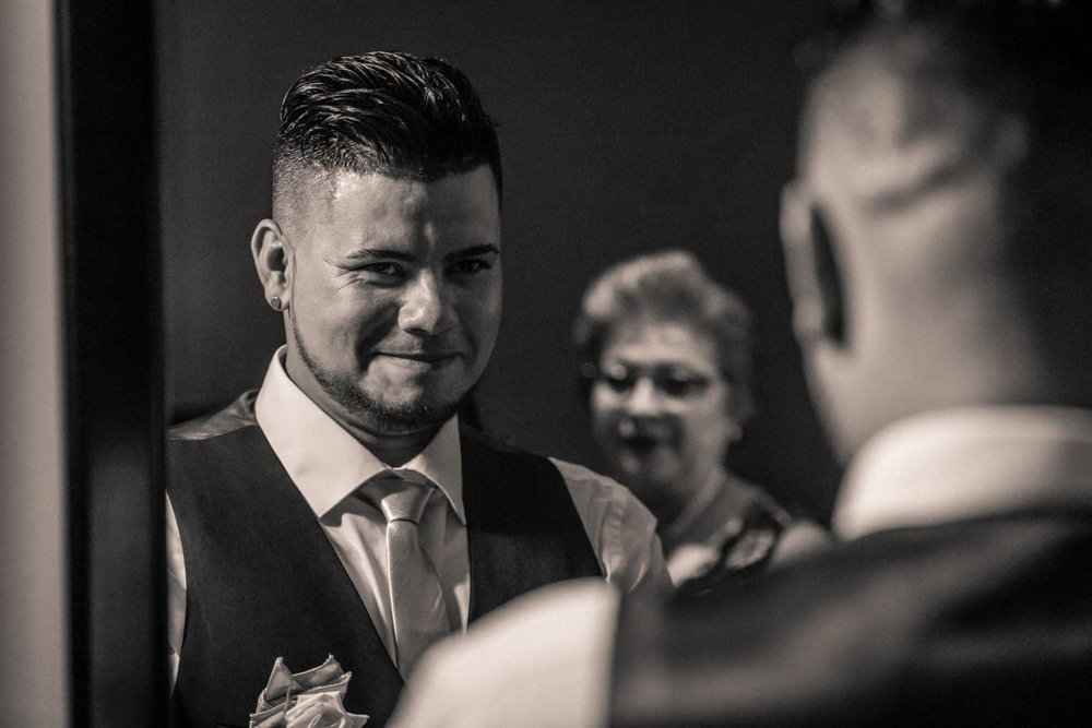 Groom preparing for wedding looks at himself in mirror with mother in background.