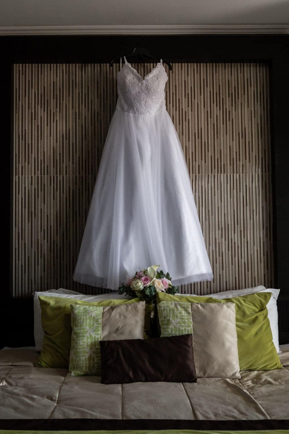 Wedding dress hanging from headboard made of bamboo in bridal suite.