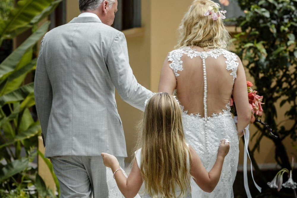Flower girl hold bride's train as she walks to ceremony site in Costa Rica.