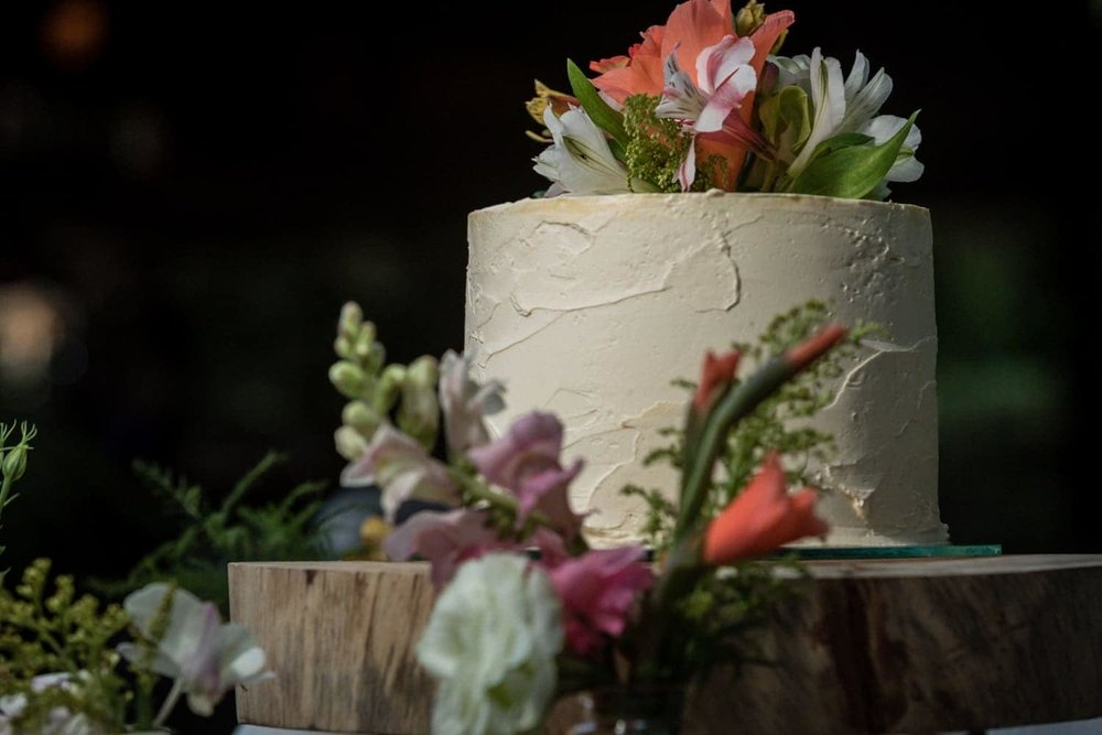 Great wedding cake with exotic flowers on thick wood table.