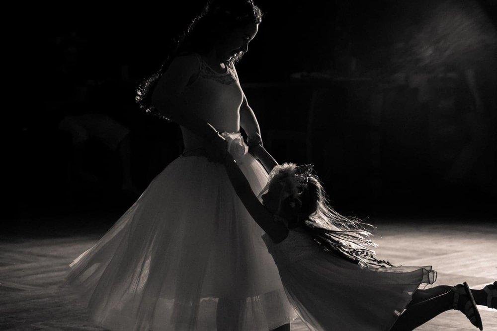 Ring bearer swings girl while dancing during wedding reception.