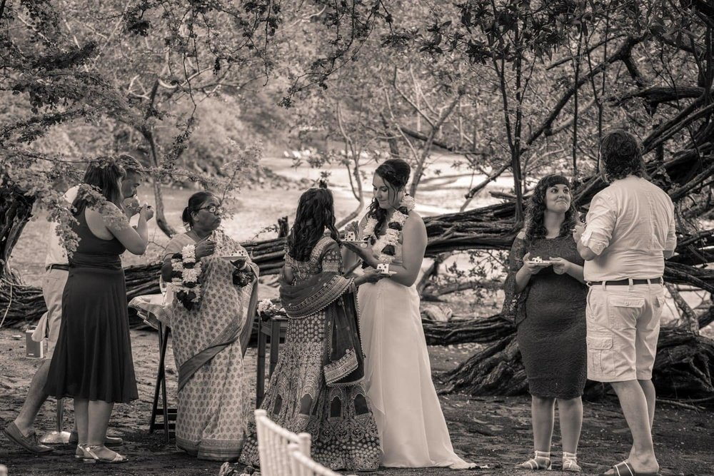 Brides' families celebrate after beach wedding ceremony at Secrets Papagayo.