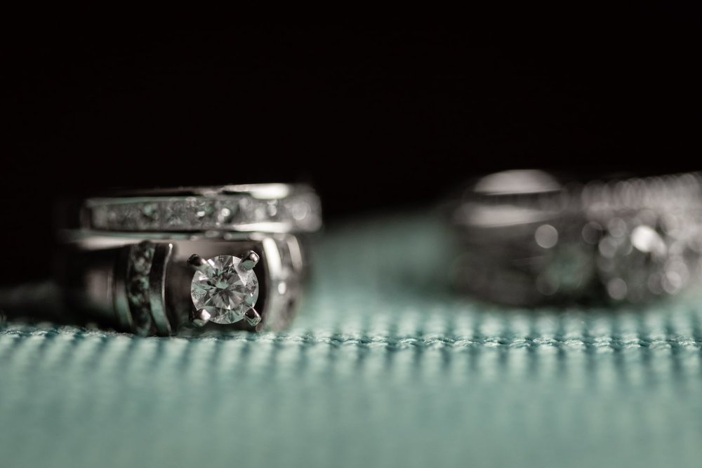 Bridal wedding bands on textured turquoise fabric in bridal suite at Secrets Papagayo.