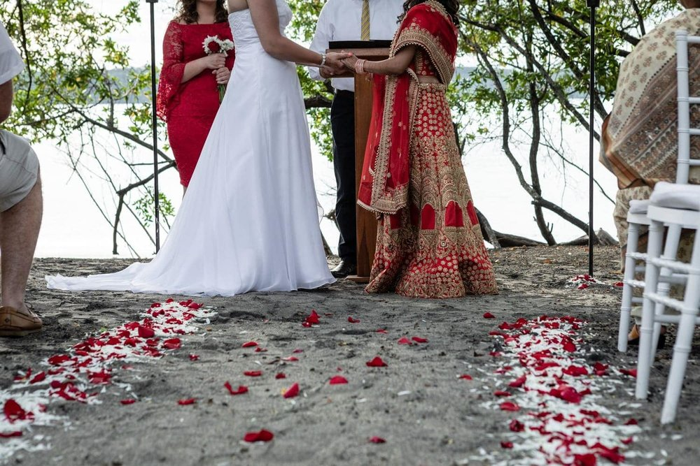 Brides standing at alter with aisle on beach decorated with red and white flower petals.