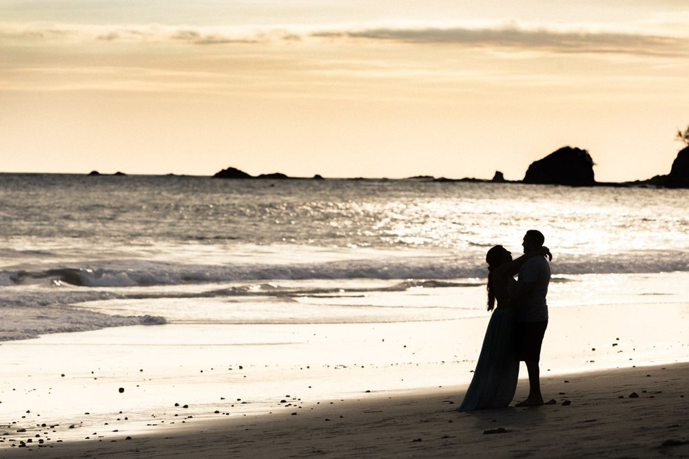 Silhouette of just engaged couple standing on shoreline at sunset in Costa Rica.