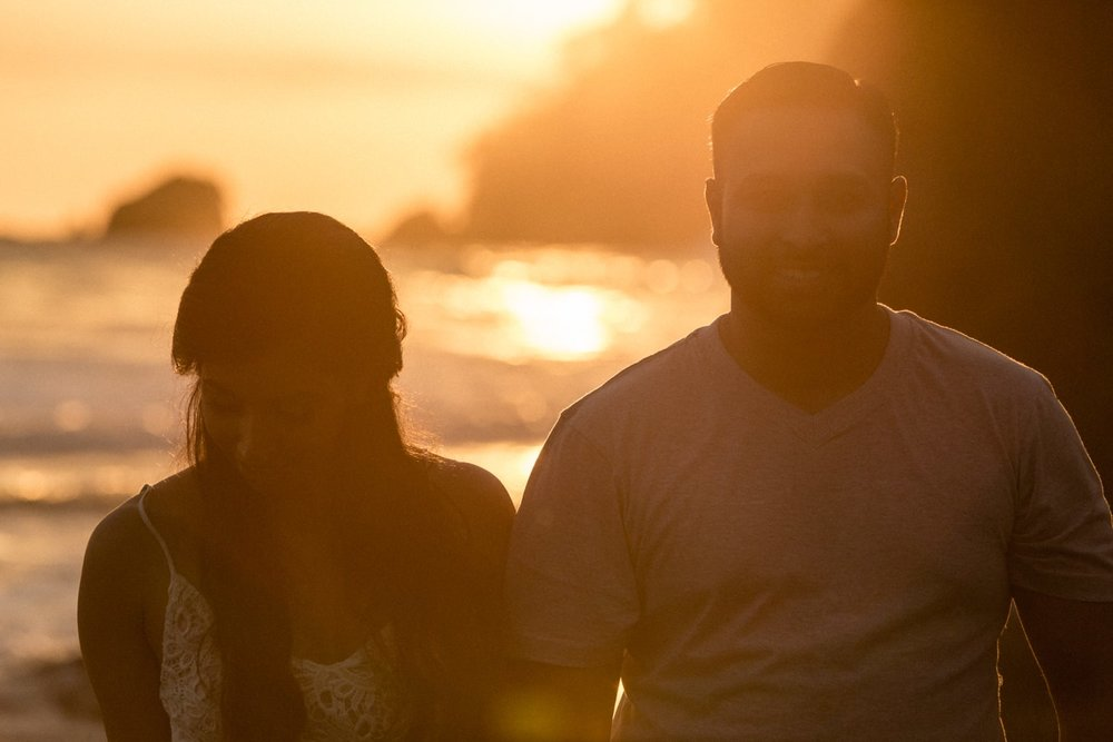 Sun sets behind a couple who just got engaged on beach in Costa Rica.