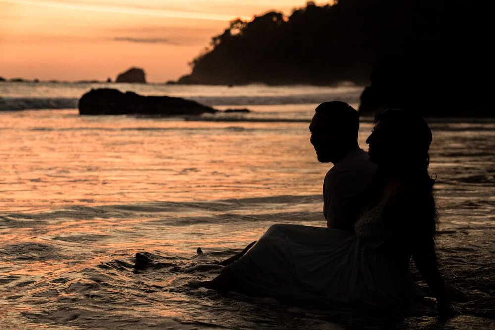 Silhouette of engaged couple sitting in water at sunset on Manuel Antonio Beach.