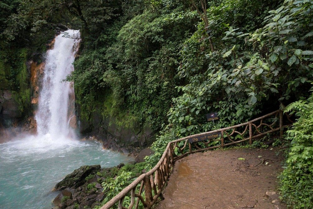 Terrace near base of Rio Celeste Waterfall is surrounding by rainforest.