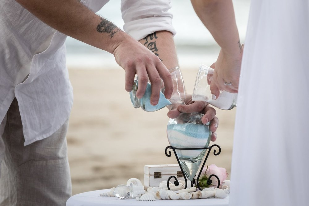 Sand-pouring ritual during beach wedding ceremony.