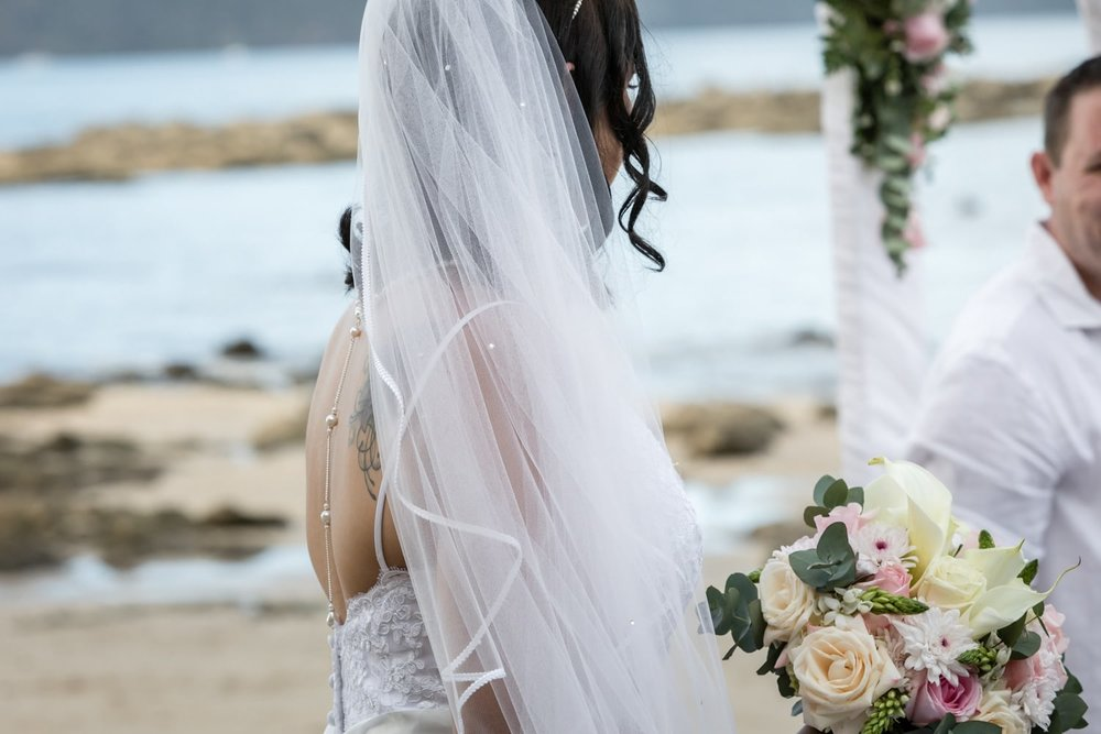 Bride on beach holding gorgeous floral bouquet .