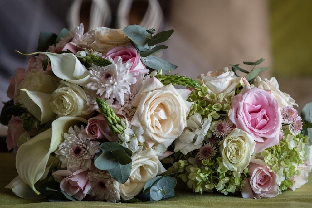 Gorgeous bridal wedding bouquets on bed in bride's suite.
