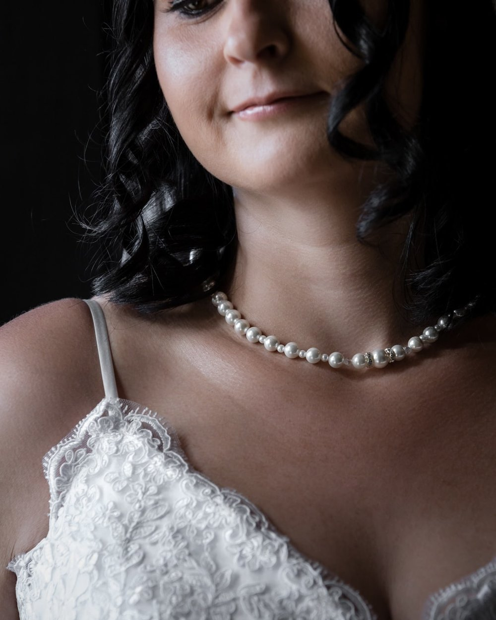Portrait of bride wearing white wedding dress and wedding-day jewelry.