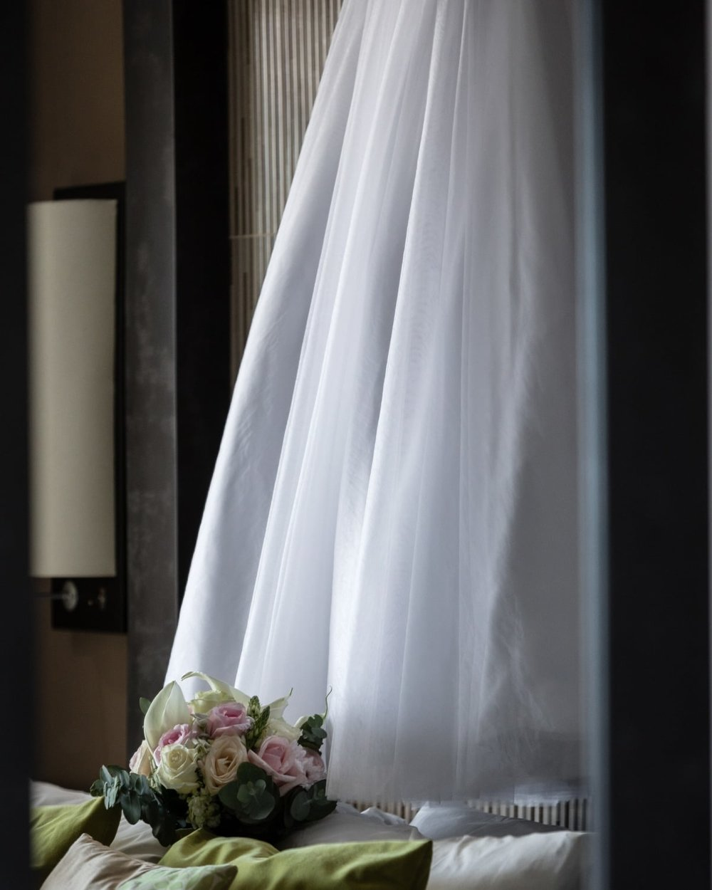 Reflection of bride's wedding dress in mirror in bridal suite.