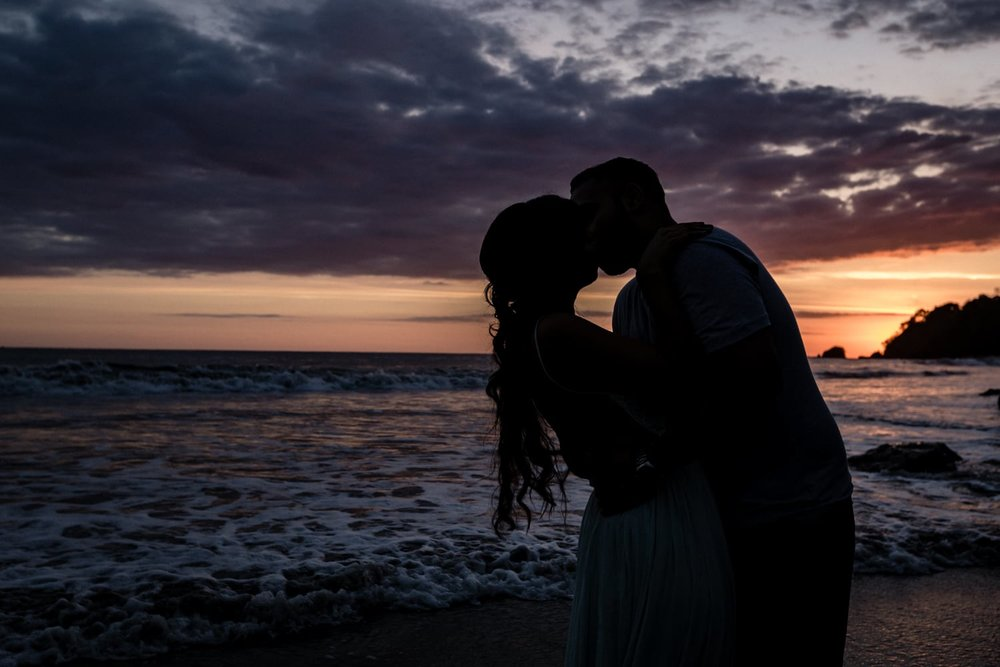 Couple having a sunset kiss on Manuel Antonio Beach in Puntarenas, Costa Rica.