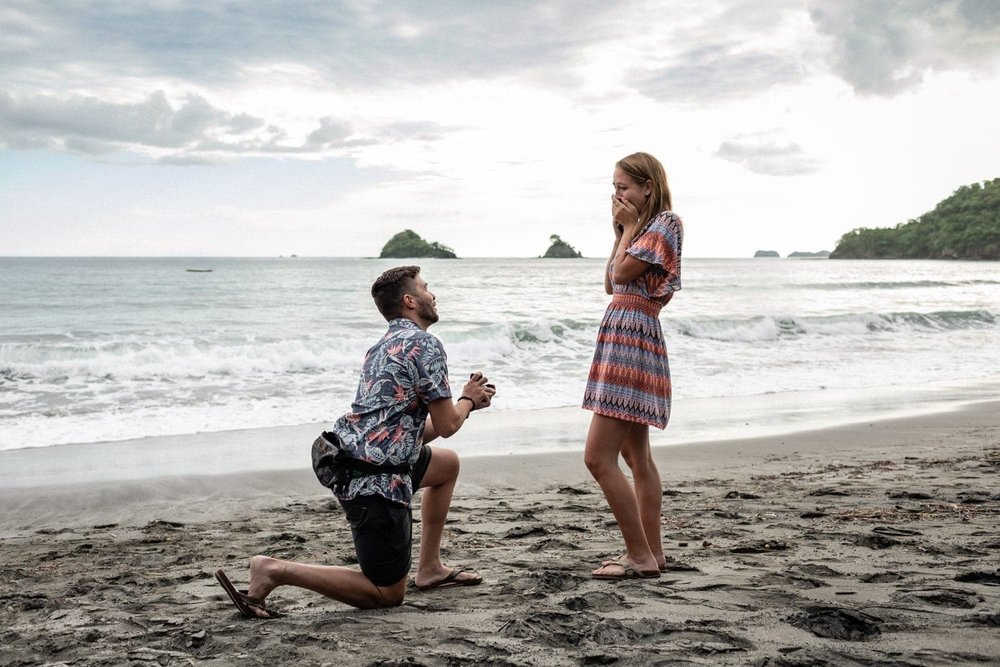 He kneels on the beach and asks for her hand.