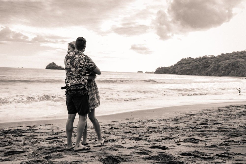 Couple hugs on beach at sunset after getting engaged on the beach.