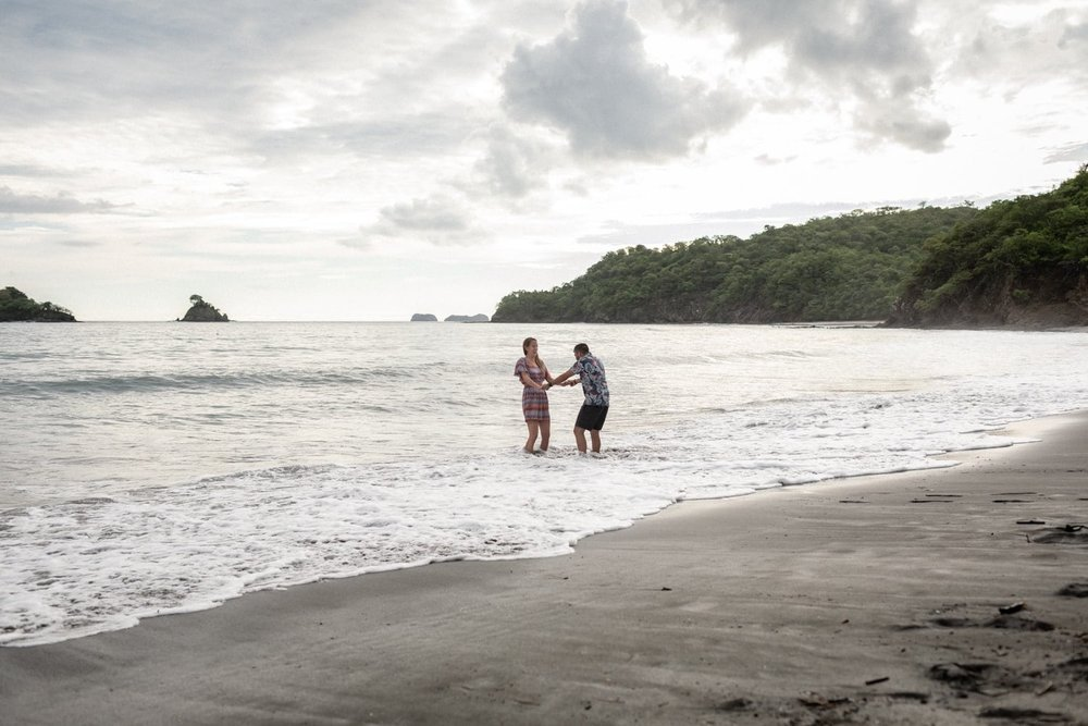 Just engaged couple has fun in the water at Las Catalinas Beach, Costa Rica.