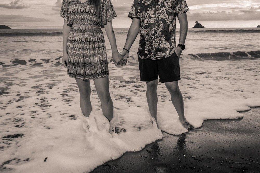 A wave washes over the feet of couple who just got engaged.