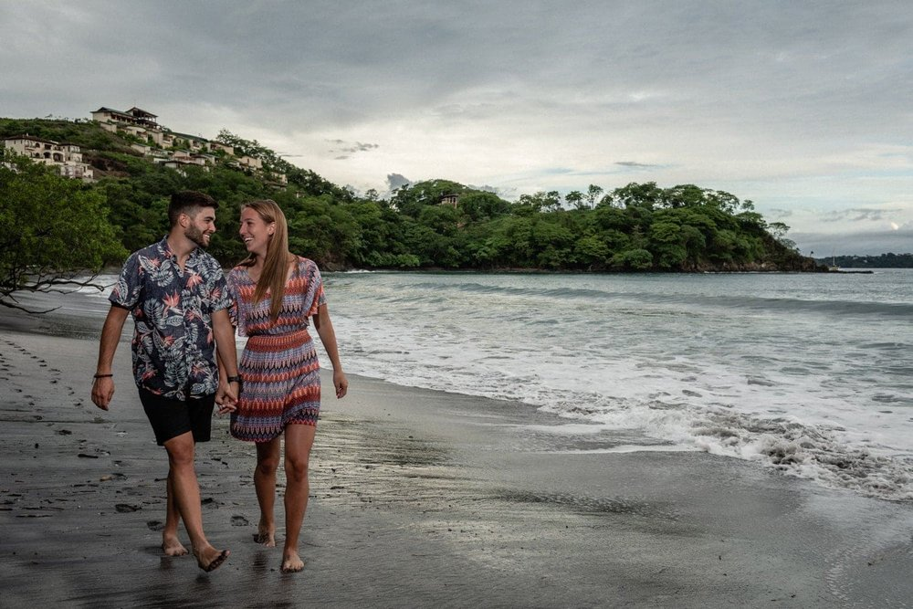 Lovers walk on the beach after getting engaged in Costa Rica.