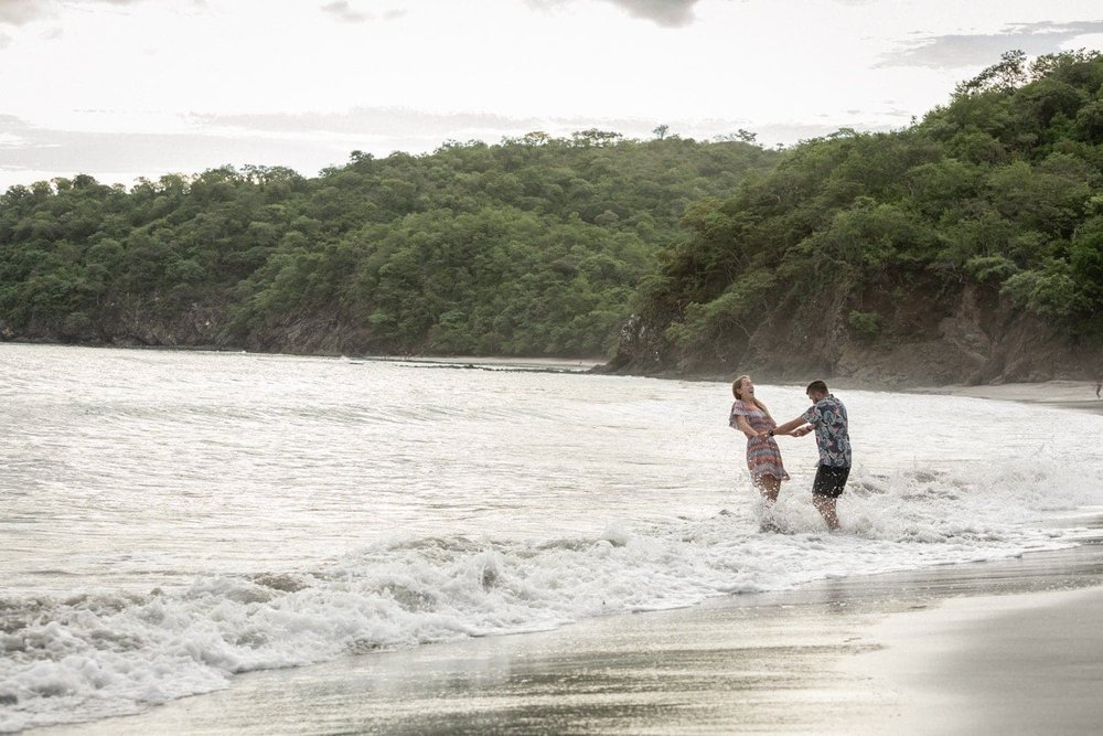 Couple having a blast in the surf on beach in Costa Rica for engagement session.