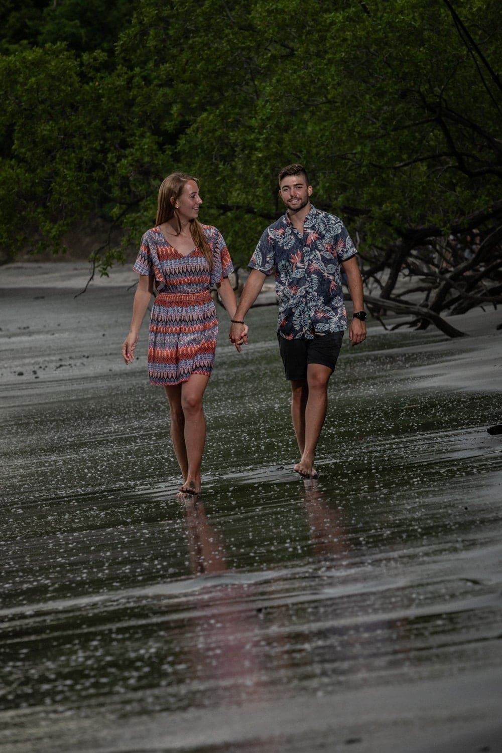 Couple walks on beach at sunset in Costa Rica after getting engaged.