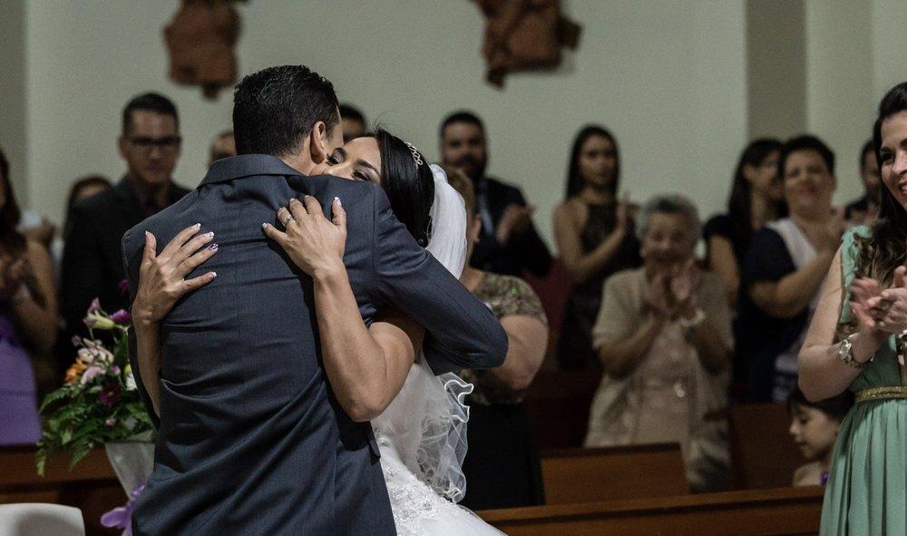 Bride and groom hug after exchanging wedding rings.