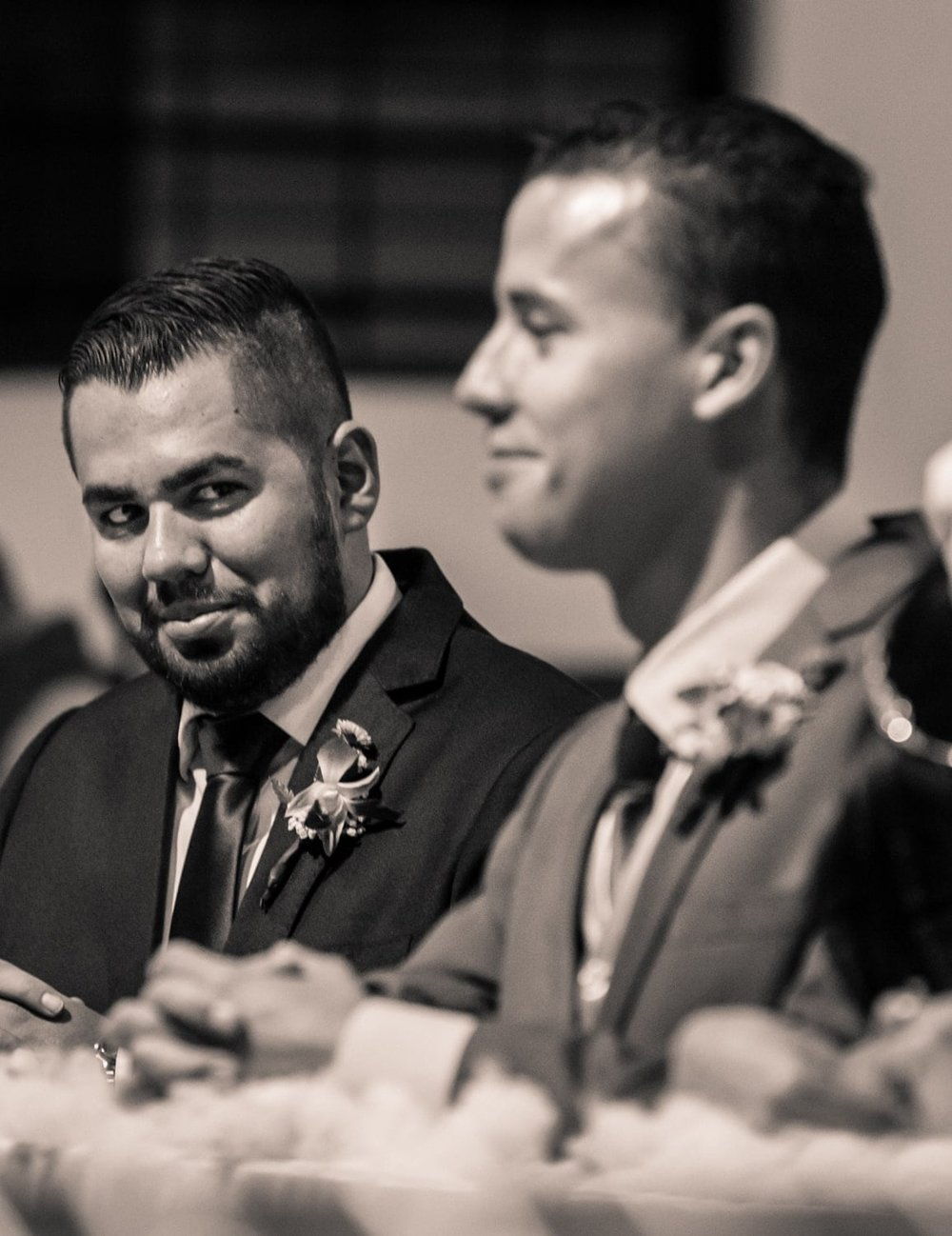 Groomsman and groom have a fun moment during wedding ceremony.