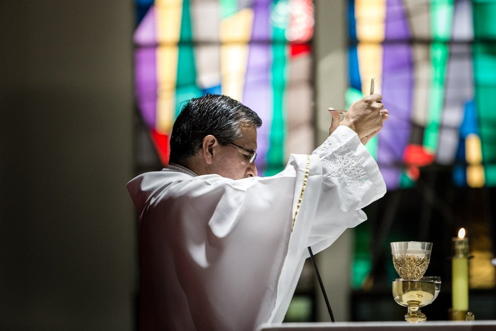 Priest performs ritual during traditional Catholic wedding ceremony.