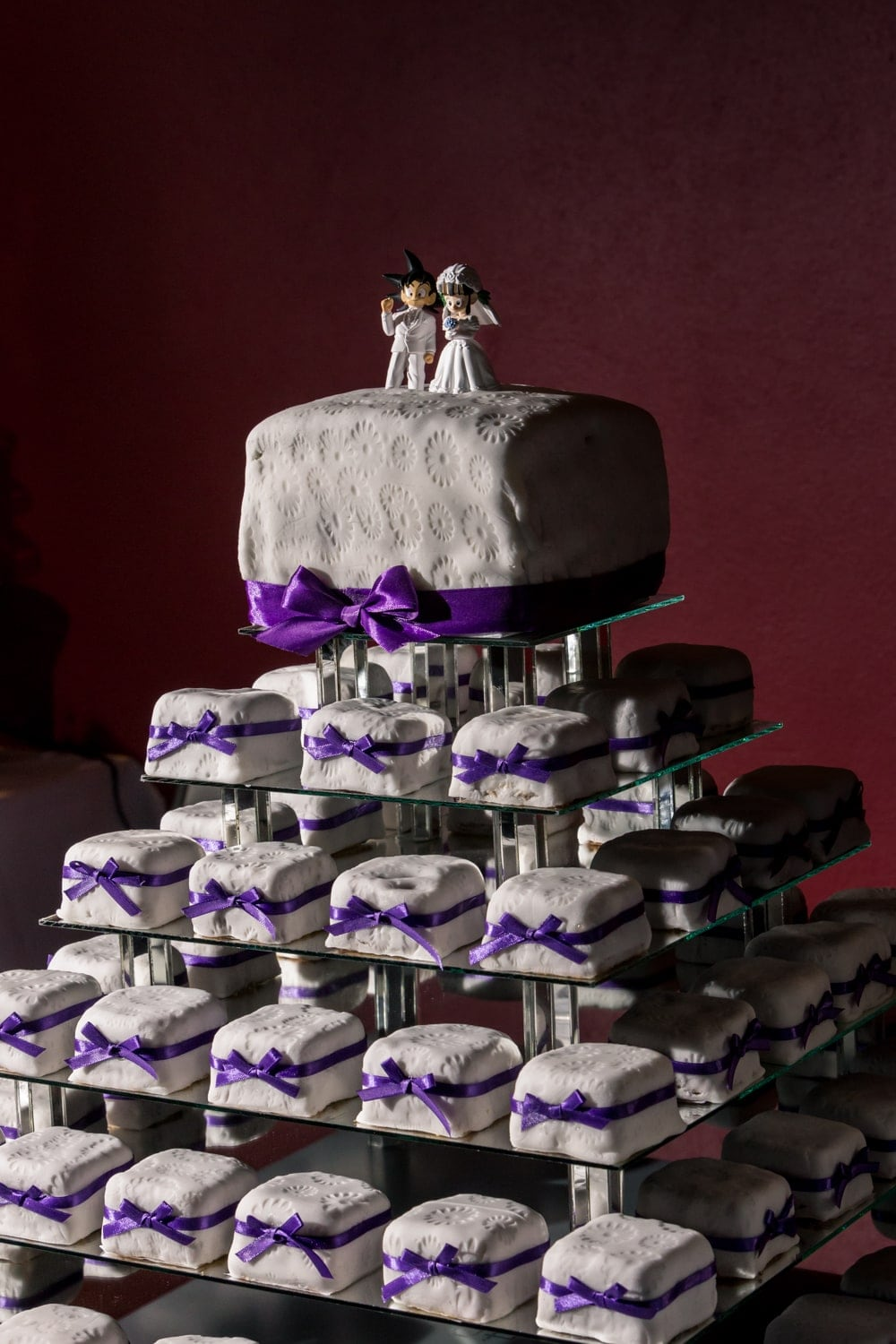 Unique white and purple wedding cake awaits hungry guests.
