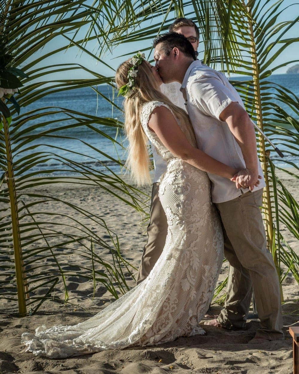 Couple kisses after saying wedding vows on beach in Costa Rica.