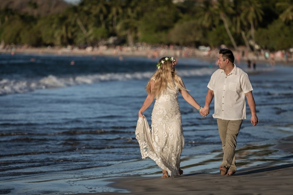 Bride and groom walking on beach in Tamarindo, Costa Rica.