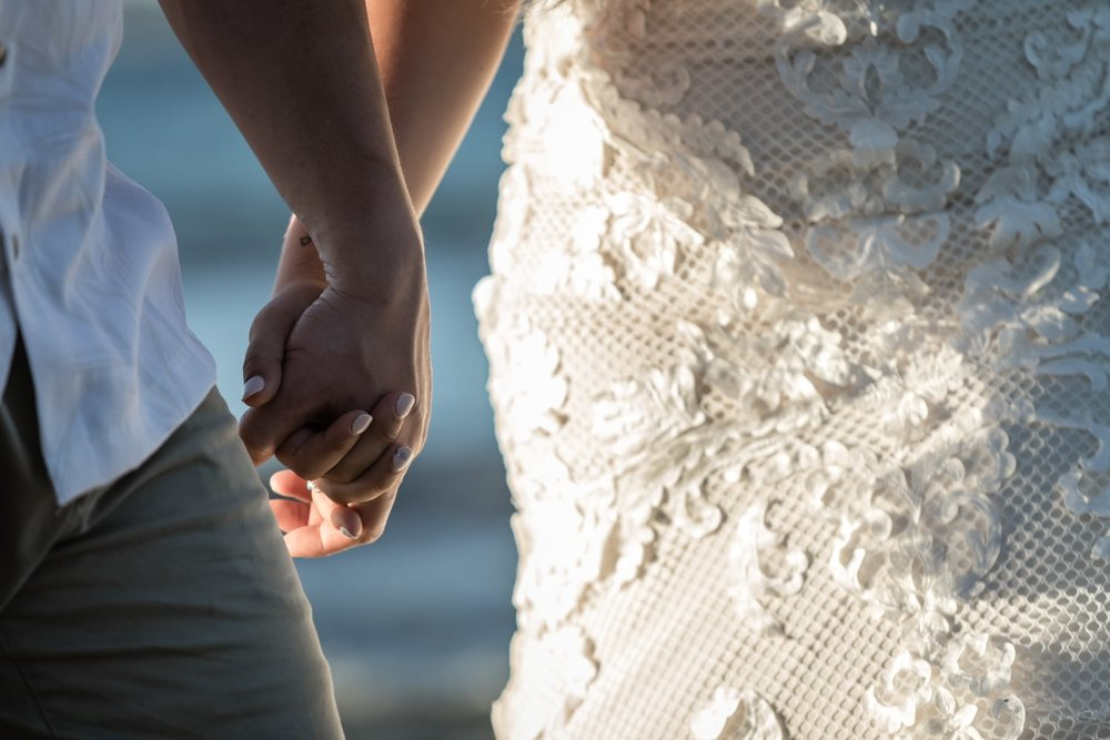 Bride and groom holding hands for beach wedding photos.