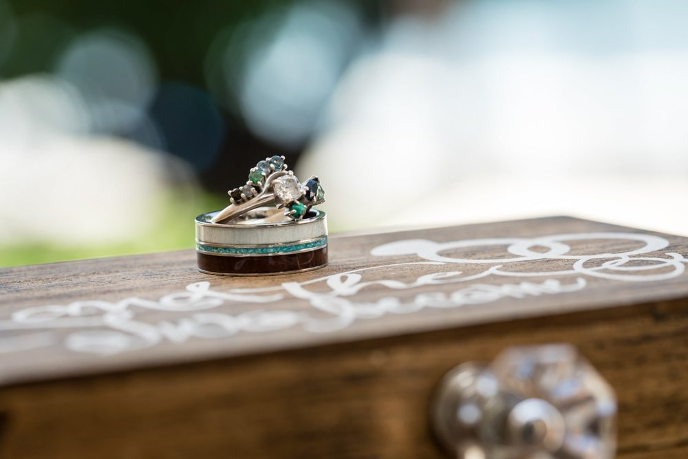 Custom wedding bands on jewelry box with beach in background.