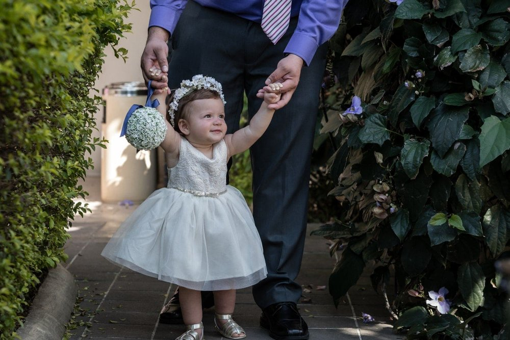 Adorable girl dressed as flower girl is escorted to wedding ceremony.