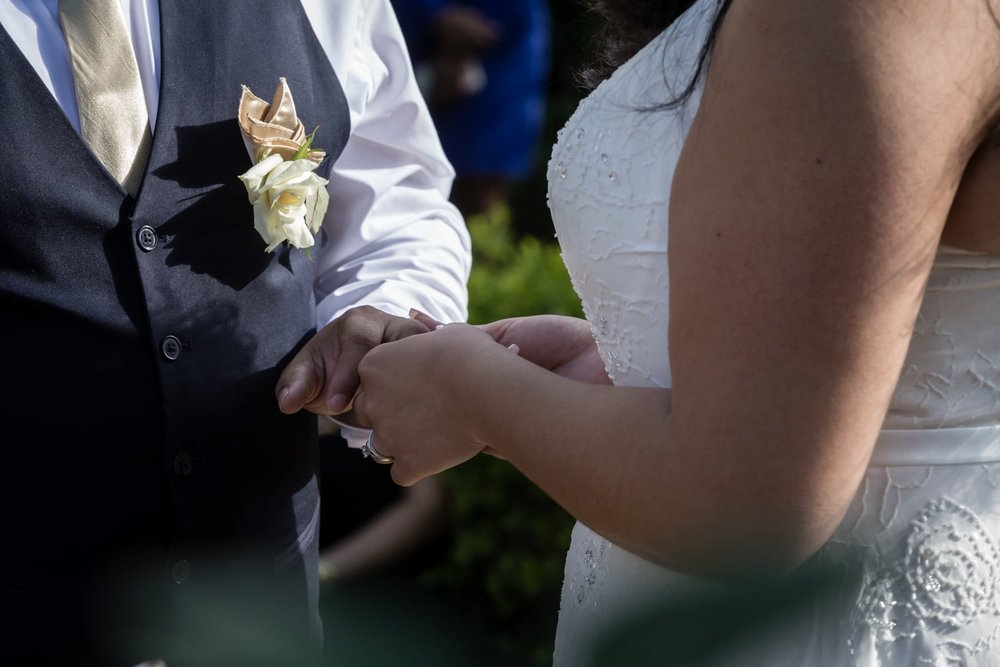 Couple exchanging wedding rings during garden wedding ceremony.