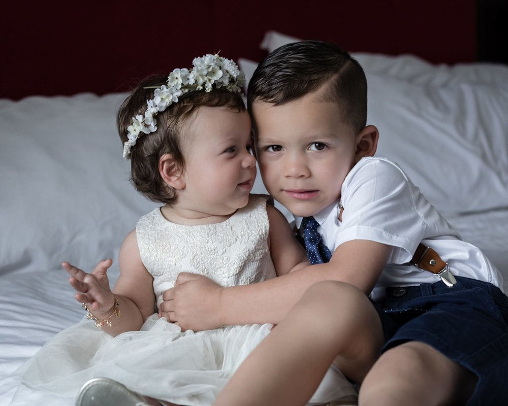 Cute kids dressed for wedding ceremony on bed in bridal suite.