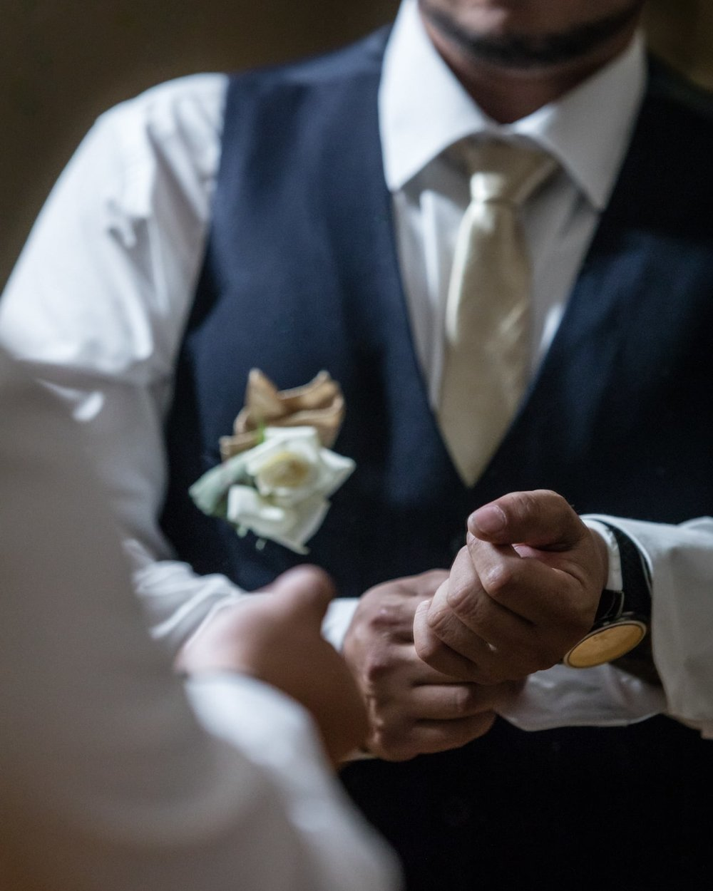 Groom wearing boutonniare preparing on his wedding day.