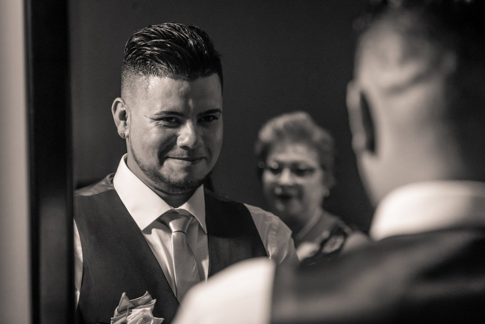 Black and white photo of groom looking in mirror while preparing for wedding.