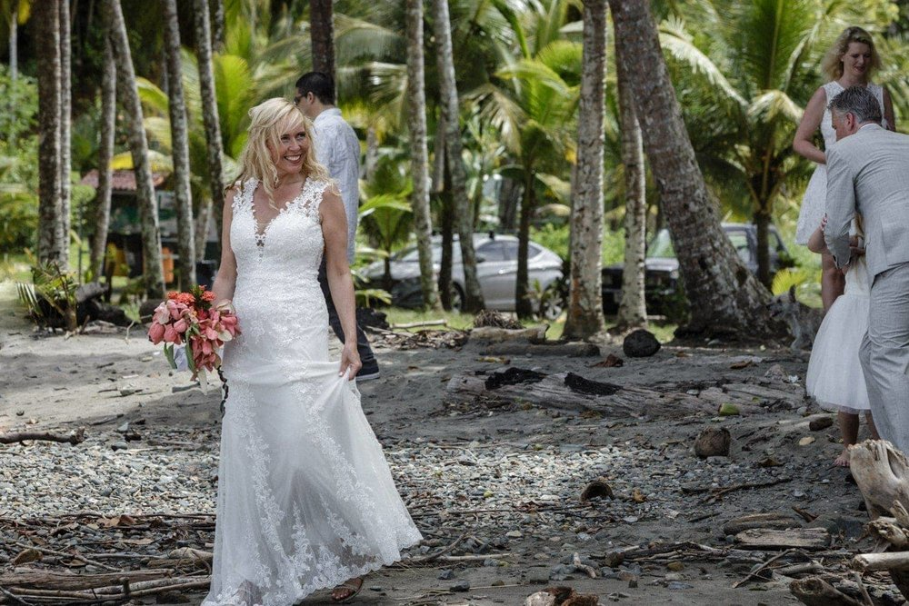 Bride walks to beach wedding ceremony venue with friends.
