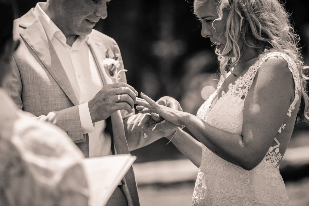 Couple exchanges wedding rings as they get married on a beach.