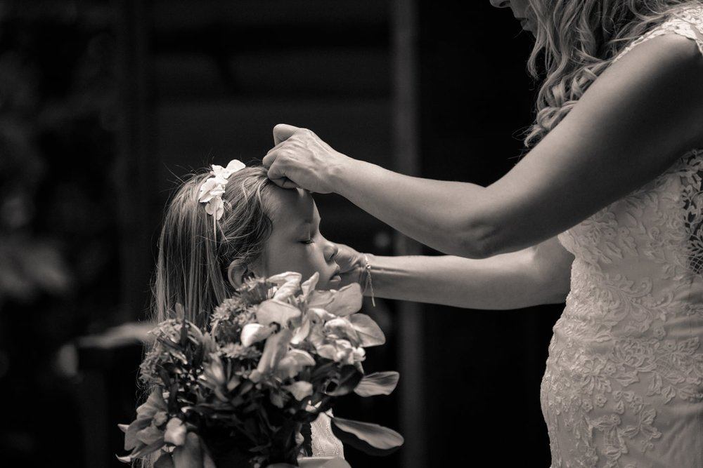 Bride helps flower girl prepare for beach wedding ceremony.